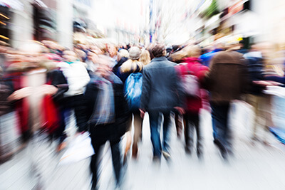 a crowd of people walks down the sidewalk