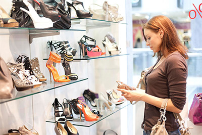 a woman stands looking at shoes in a retail store