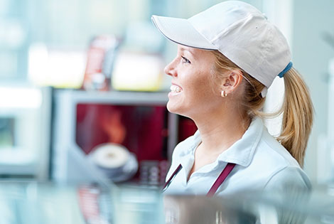 a girl with a uniform and hat on stands behind a fast-food counter