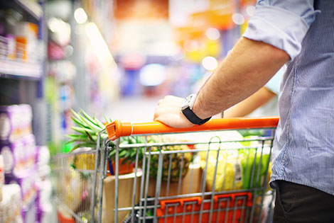 a man pushes a grocery cart down a supermarket aisle
